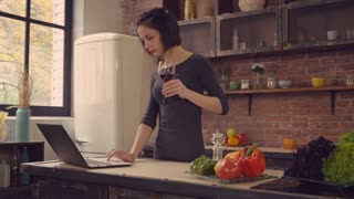 Happy young woman drinking red wine at home. Lady standing near the big window in the kitchen using laptop surfing internet. Businesswoman looking on the screen read or order delivery food she could