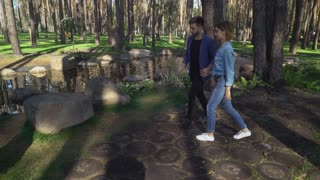 Happy young woman walking with boyfriend at the park with lake and big stones. Caucasian girl wearing in casual denim shirt jeans sneakers handsome friendly guy dressed in blue stylish jacket. Smiling