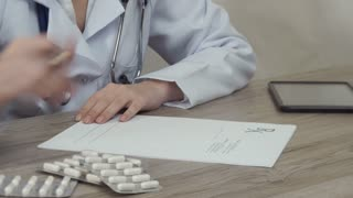 he doctor looks at tablets and writes a prescription.