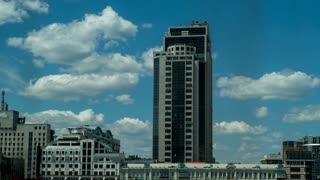 In the city center there is a modern office building, the sky floating clouds, a sunny day. timelapse in high resolution