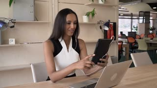 Indian female has remote meeting with client via internet. Mixed race business woman smiling her interlocutor and give advice. Young professional worker using app on modern gadget for negotiation with