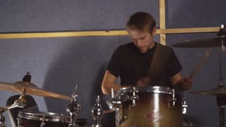 Instrumentalist rock or pop musician wearing in casual black t-shirt. Portrait caucasian man playing on drum kit. Drummer guy plays on the drums set on his young face we can see different emotions