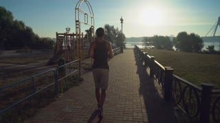 Jogger runs outdoor at sunrise in summer. Rear back view runner jogging along sports ground. On the background river and urban bridge. Man wearing in sport shorts and t-shirt. Workout at the open air