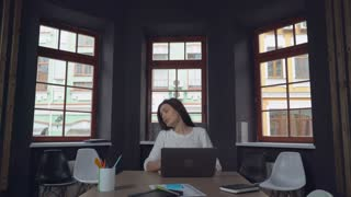 Leader of business group makes a comment and editing pointing some important data in project. Businesswoman sitting at the desk two young professional workers coming to the office. Man wearing in