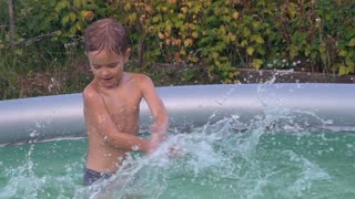 Little boy playing in the swimming pool. Happy smiling child enjoy summer outdoors. Caucasian baby squirting blue water at the backyard