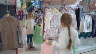 Little girl trying on clothes in the shop. Happy customer standing in front of mirror holding two beautiful dress in the store. Smiling blonde customer buying in the shopping center. female child with