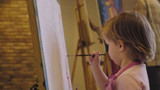 Little girl with short hair in a pink shirt and aprons draws paints on a canvas in a studio