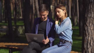 Man and woman using laptop outdoors. Happy couple on the meeting or date looking on the computer screen smiling. Handsome guy and attractive girl sitting on the bench in the park