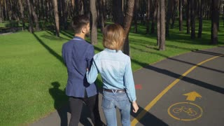 Man and woman walking on the pedestrian zone rear back view. The road divided with sign part for cyclists and for pedestrians. couple woman and man walking outdoors. Pair talking smiling laughing on a
