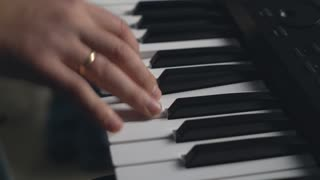 Man fingers on the synth electronic musical instrument close up details. Guy hand playing strums a chord on the synthesizer. Amr on the musical keyboard. performs at a concerto or rehearsing in the