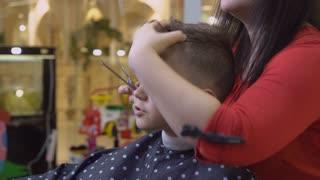 Man hairstyling in hairdressing salon. Portrait happy little boy in hair salon. Attractive hairdresser cutting hair client