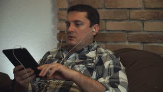 Man in earphone talking through tablet
