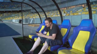 Man on the empty sports soccer stadium using smartphone. Young male sitting on a benchwarmers near the football field. Chair on bench in front of gridiron blue and yellow colors. Guy wearing in casual