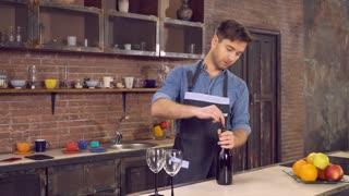 Man opening bottle of wine at home. Young caucasian guy stands on the kitchen wearing in shirt and apron using corkscrew. On the cook table two wineglass