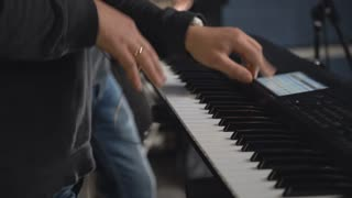 Man plays on the synthesizer switch something on the touch screen. Close up details keyboardist hands play synth electronic musical instrument. concert or rehearsal rock or pop band. On the background