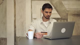 Man sitting in the cafe drinking coffee and booking tickets via internet. Male smiling and happy. Guy pays by credit card