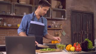 Man standing on the kitchen at home alone. Handsome husband cutting ingredients for salad. Happy smiling guy wearing an apron and blue shirt cooking dinner. On the cook table laptop with recipe dish