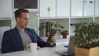Man using app on touch screen tablet. Guy happy and smile in his office. He says hi and talking with client emotionally