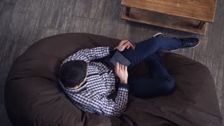 Man with tablet and credit card lying on the couch
