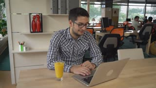 Man works in modern room. Young guy wearing in casual shirt. On the wooden table glass with orange juice. On the background business meeting with colleagues