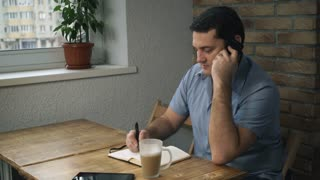 Manager in a blue shirt sitting in cafe, talking on phone, taking notes on a pad. On the table is a cup of latte next to the diary is a tablet