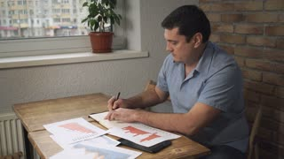 Manager sitting at desk, taking notes in a notebook, on a table scattered papers