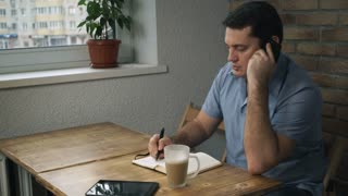 Manager sitting in cafe, talking on phone, taking notes on a pad