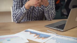 man's hands holding paper documents with financial charts. Close-up details man working with sales or marketing report. Invisible guy sitting at the working place with computer on wooden desk