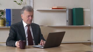 Middle aged businessman sitting at the working place in the office with wooden desk. Grey haired man using computer drinking coffee at work. Silver leader holding cup with drink. White headed manager