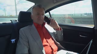 middle aged businessman talking on the smartphone using laptop on the back seat in car . adult man with white hair wearing in elegant suit and red shirt rides with driver to work. City view with urban