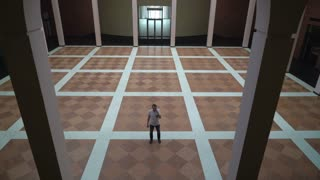 Middle-aged man standing in a large circle with columns, talking on the phone and goes to the door