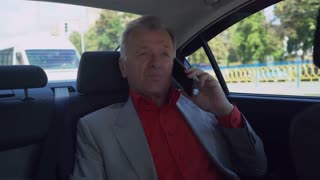 Middle aged man talking on the smartphone in car. businessman in years sitting on backseat using mobile wearing in grey suit