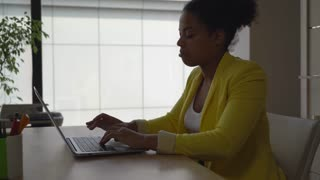 Mixed race business woman working in modern office with big windows. Young professional lady typing on computer wearing in yellow stylish jacket