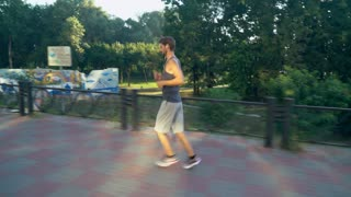 Mixed race man jogging on the pavement along park. Jogger at the morning runs in the city with urban view and green trees. Guy wearing in sport shorts and t-shirt run sneakers listening music with