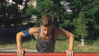Mixed race man push- ups outdoors workout. Training exercises challenge for forearms, biceps and triceps at the outdoor gym. Male wearing in sport t-shirt listen music with earphones at the open air