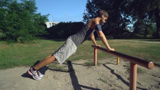 Mixed race man push- ups outdoors workout. training forearms, biceps and triceps at the outdoor gym. Handsome guy trains in city park at summer season. Model wearing in sport shorts and t-shirt listen