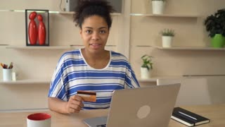 Mixed race woman shopping online. satisfied customer buy remote using internet and laptop holding credit card