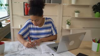 mixed race worker in architectural agency working with sketch holding pencil and ruler. Young professional woman sitting at the desk
