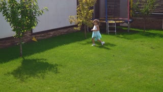 Mother play with little daughter in the garden. Adult caucasian woman running with cute blonde baby on lawn with green grass at the backyard near the house. Young happy female catching up cute girl 3