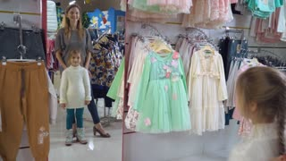 Mother with daughter choosing clothes in the shopping mall. Happy family buying in emporium. Adult caucasian lady with little girl standing in front of mirror holding rack with dress. Smiling