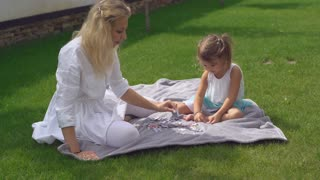 Mum and child play with puzzles outdoors. Young caucasian woman sitting with daughter on the lawn with green grass. Smiling baby with mom playing in the garden at the backyard near the house