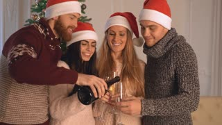 new years party. Happy friends celebrating smiling toasting. Handsome man with beard pours champagne in glasses. People enjoy celebrate standing near christmas tree wonderful decorate