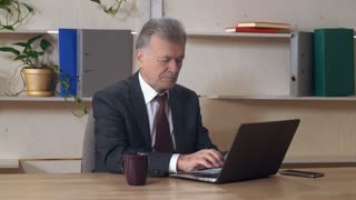 Old man in years surfing internet and typing on keyboard laptop in contemporary office. Old-aged boss working with computer. Grey headed manager wearing in black fashionable suit reading document