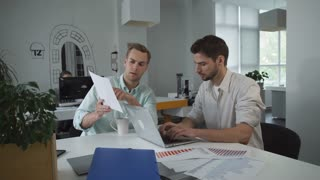 One handsome man typing on laptop another businessman holding documents with diagram and explain. On the table documents with charts and sales report. Coworkers work in a stylish contemporary office