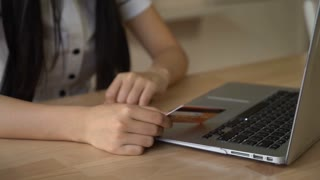 Online shopping details. women's hands typing number security code on the computer. Woman holding credit card. On the table laptop