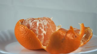 Peeled mandarin slices on a plate spinning