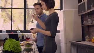 People cooking dinner on the kitchen. Happy caucasian woman and man smiling talking drinking wine at home. Family wearing in casual dress enjoy day off at home. Apartment with loft interior