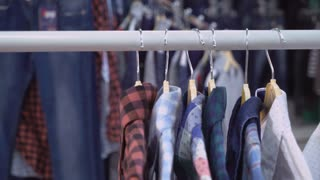 Person man or woman choosing shirt in the store. Close up details hand holding clothes on the rack. Hanger standing in the shop with colored garment