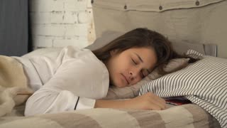 Portrait adult woman sleeping in the bed. Pretty girl waking up and looking on screen smartphone. Lady with happy smile looking at the camera in bedroom in the morning