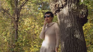 Portrait adult woman smoking cigarette in the park or forest. Girl with short black hair standing near the huge tree wearing in casual pullover. Breathtaking landscape in sunny day with yellow leaves in autumn season.